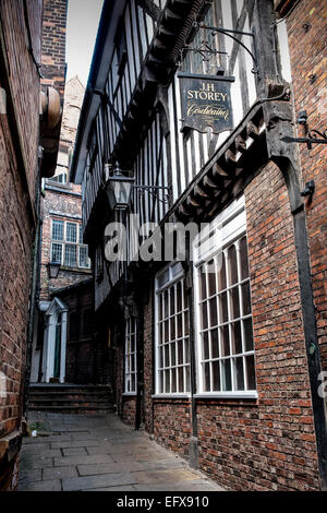 Lady Peckett's Yard, York, UK. An old sign for a cordwainer (shoemaker) is high up on a wall in a narrow alley. - Stock Photo