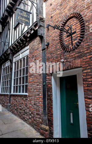 Old cordwainer's shop sign high up a brick wall, in a narrow alley alleyway ginnel in Lady Peckett's Yard, York, - Stock Photo