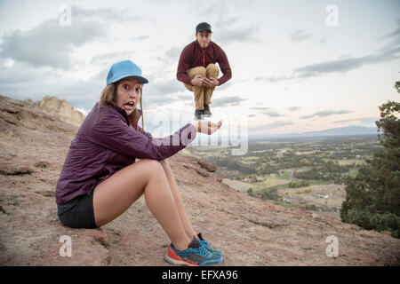 Young man jumping mid air on top young womans hand,  Smith Rock, Oregon, USA - Stock Photo