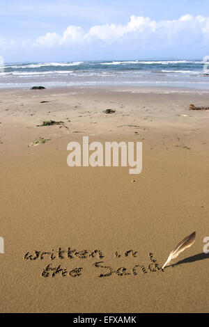 a feather used as a quill pen to write written in the sand on an irish coastal beach - Stock Photo
