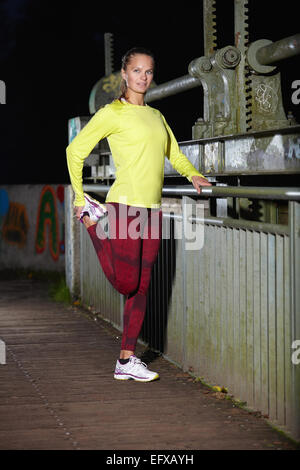 Young woman warming up on footbridge at night - Stock Photo