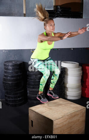 Young woman jumping onto box in gym - Stock Photo