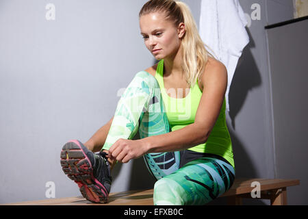 Portrait of young woman tying trainer laces in gym - Stock Photo