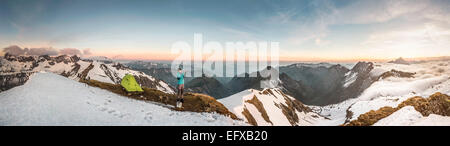 Panoramic of young male mountain trekker photographing on smartphone in Bavarian Alps, Oberstdorf, Bavaria, Germany - Stock Photo