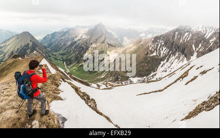 Young male mountain trekker photographing valley on smartphone in Bavarian Alps, Oberstdorf, Bavaria, Germany - Stock Photo
