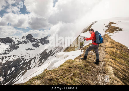 Young male mountain trekker looking from ridge in Bavarian Alps, Oberstdorf, Bavaria, Germany - Stock Photo