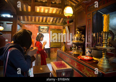 People praying at the shrine inside the Japanese covered bridge, Hoi An, Vietnam. - Stock Photo