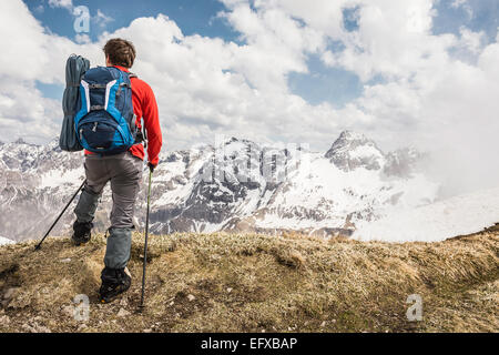Young man looking at view in Bavarian Alps, Oberstdorf, Bavaria, Germany - Stock Photo