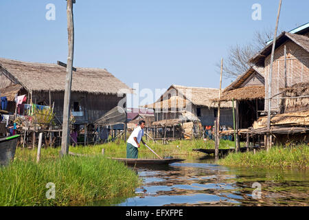 Intha man in proa at village with traditional bamboo houses on stilts in Inle Lake, Nyaungshwe, Shan State, Myanmar - Stock Photo