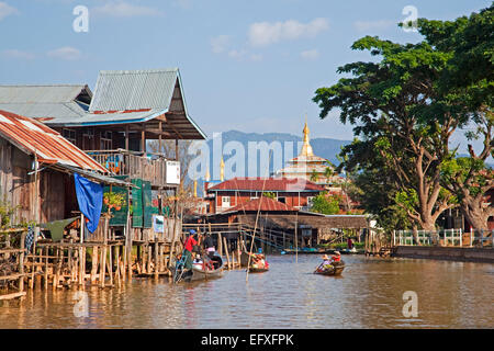 Intha villagers in proas at lakeside village with bamboo houses on stilts and Buddhist temple, Inle Lake, Myanmar - Stock Photo
