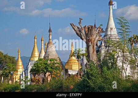 Golden and white Buddhist Stupas on the shore along Inle Lake, Nyaungshwe, Shan State, Myanmar / Burma - Stock Photo