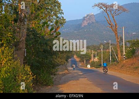 Tourist cycling towards Buddhist monastery on summit of Taung Kalat near  volcano Mount Popa, Mandalay state, Myanmar - Stock Photo