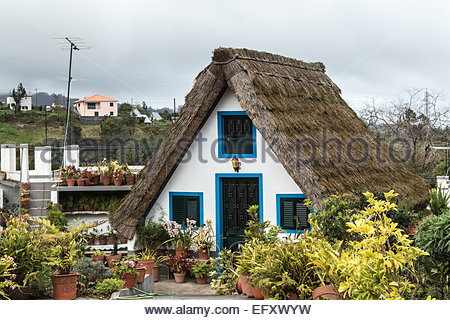 An occupied traditional triangular straw thatched house known as a Palheiros in Santana Portugal. - Stock Photo