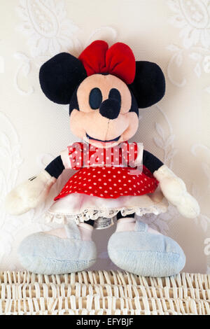 Minnie Mouse in red polka dot dress soft plush cuddly toy standing on wicker basket - Stock Photo