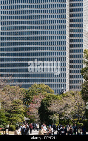 Tokyo, Japan. Towering office blocks overlook the East Gardens of the Imperial Palace - Stock Photo