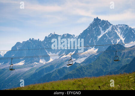 Chairlift with Aiguille du Midi mountain range behind, Chamonix, French Alps, France, Europe in summer - Stock Photo