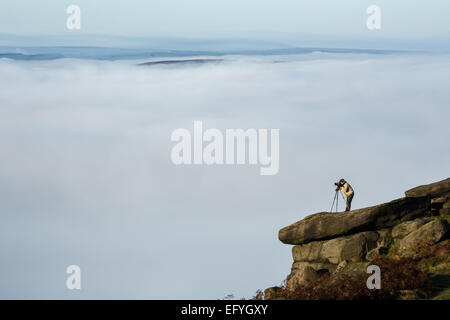 A photographer captures a temperature inversion from Higger Tor in the Peak District. - Stock Photo