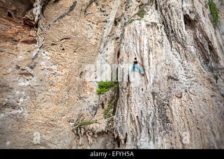 Young female rock climber on incredible wall, Railay Beach in Thailand. - Stock Photo
