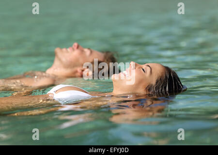 Profile of a couple of tourists swimming in the sea of a tropical resort floating on the turquoise water on summer - Stock Photo