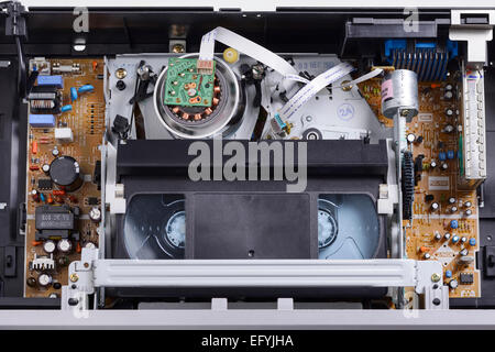 The inside of a VHS video cassette player with a tape laced around the playing head - Stock Photo