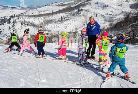 Eight young first-time skiers take a group lesson with a Beaver Creek Ski School instructor on a snowy slope in - Stock Photo