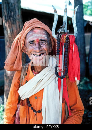 An elderly almost-toothless Hindu holy man in well-worn clothing holds a metal trident and smiles for tourists in - Stock Photo