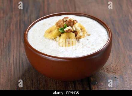 Oatmeal porridge with walnuts and bananas in ceramic bowl, close up view - Stock Photo