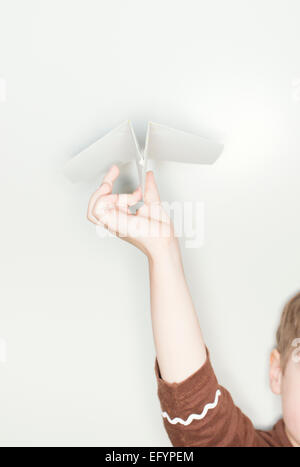 Hand of child holding paper airplane. - Stock Photo
