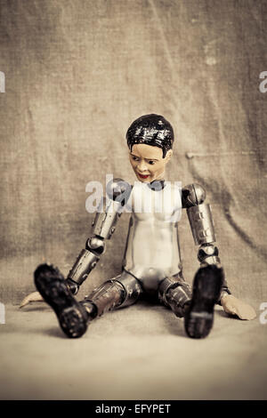 Pensive and depressed male toy doll sitting and looking down. Old fashioned retro design. - Stock Photo