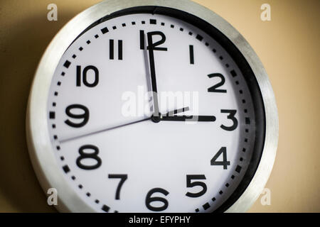 Clock on the wall showing the time of 3 O'Clock - Stock Photo