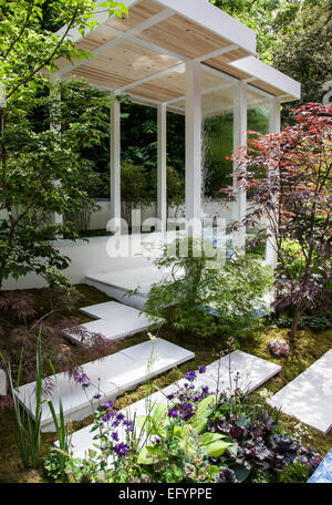 White pavilion with in-built water wall and stepping stone with Japanese style planting featuring Acer japonicum - Stock Photo