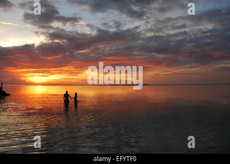 A couple stands in the sunset; Florida Keys, MM88. - Stock Photo