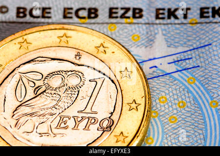Greek 1 Euro coin on a €5 note - Stock Photo