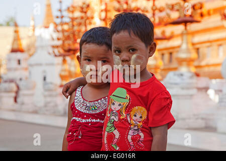 Two Burmese children wearing thanaka / thanakha on their cheeks, a yellowish-white cosmetic creamy paste, Myanmar - Stock Photo