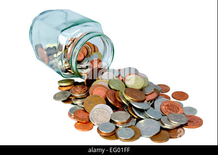 cut out of Glass jar full of uk British coins spilling on white background - Stock Photo