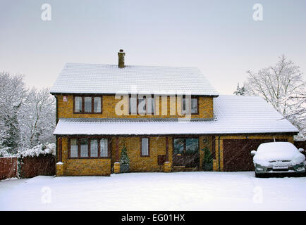 Day time image of large executive style detached house covered in snow - Stock Photo