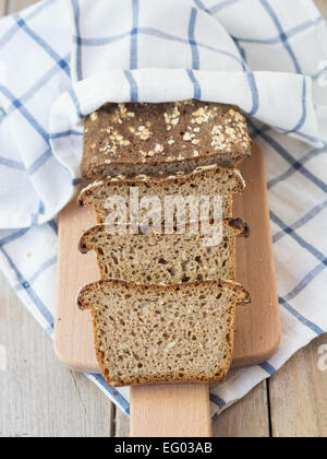 Vertical photo of sliced homemade whole grain mixed rye-wheat sourdough bread with seeds on a cutting board. Overhead - Stock Photo