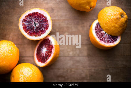 Blood oranges whole and sliced on a rustic wood cutting board. - Stock Photo