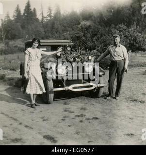 Dallas, Usa. 12th Dec, 2014. CIRCA 1931: Reproduction of an antique photo shows couple posing near the car, the - Stock Photo