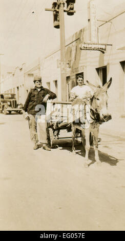 Usa. 12th Dec, 2014. CIRCA 1930s: Reproduction of an antique photo shows two men posing beside the wagon, which - Stock Photo