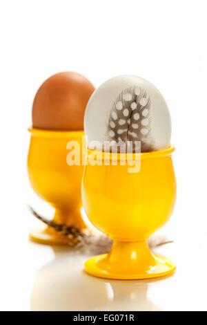 eggs  in yellow eggcups  isolated on white - Stock Photo