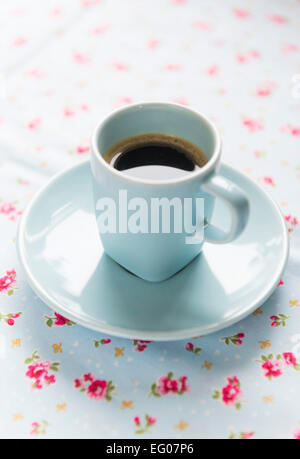 Espresso coffee in a blue cup and saucer on a floral table cloth. - Stock Photo