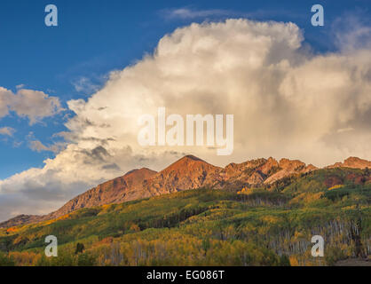 Gunnison National Forest, CO: Storm cloud in afternoon light over the Ruby Range with early fall colors on aspen - Stock Photo