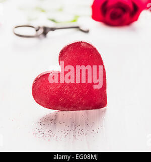 Big red wooden heart over rose and key background, white valentines day card - Stock Photo
