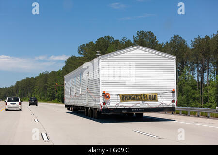 Truck with oversize load: moving a FEMA Trailer Home Unit on the I-85 Interstate highway near Grantville GA. - Stock Photo