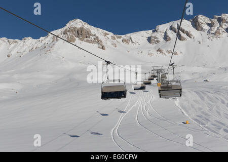 Snowboarders and skiers riding up a ski lift in Dolomites, South Tyrol, Italy - Stock Photo