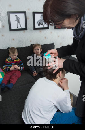 Mother checking childs hair for lice - Stock Photo