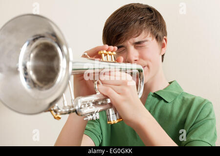 Photo of a young teen playing his silver trumpet. - Stock Photo