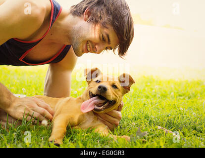 Smiling man lying on grass stroking his puppy dog - Stock Photo