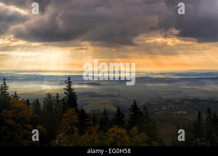Godly light rays passing through clouds in the early morning above hilly countryside - Stock Photo